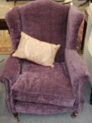 A purple upholstered wing armchair in the Georgian style