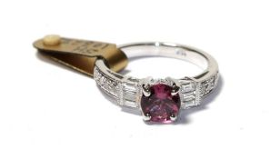 A tourmaline and diamond ring, the round cut pink tourmaline flanked by trios of baguette cut