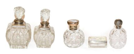 Four George V cut glass scent bottles with silver mounts, together with a Victorian cut glass and