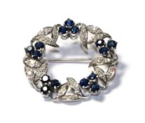 A sapphire and diamond brooch, realistically modelled as a wreath, clusters of three round cut
