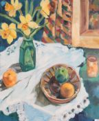 Anne Mendelow (b.1945) Still life of daffodils in a green vase and fruit on a white tablecloth
