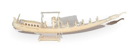 A 19th century Indian carved ivory model of a boat with figures, 45cm long