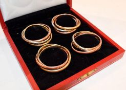 A cased set of four silver plate and gilt plate napkin rings, retailed by Cartier, 20th Century,