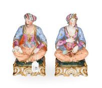 A pair of Paris porcelain figures formed as a seated Turk and his companion, raised in gilt Rococo