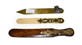 A brass mounted olive wood page turner, a brass ruler mounted with a metal spaniel and another
