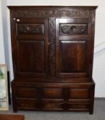 Period oak linen cabinet of pegged construction and raised on three drawer base, 148cm by 54cm by