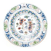 An English Delft plate, mid 18th century, painted in colours with a central flower spray within
