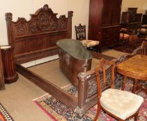 A Late 19th Century Carved Walnut Bedstead, the headboard with moulded canopy centred by a mask