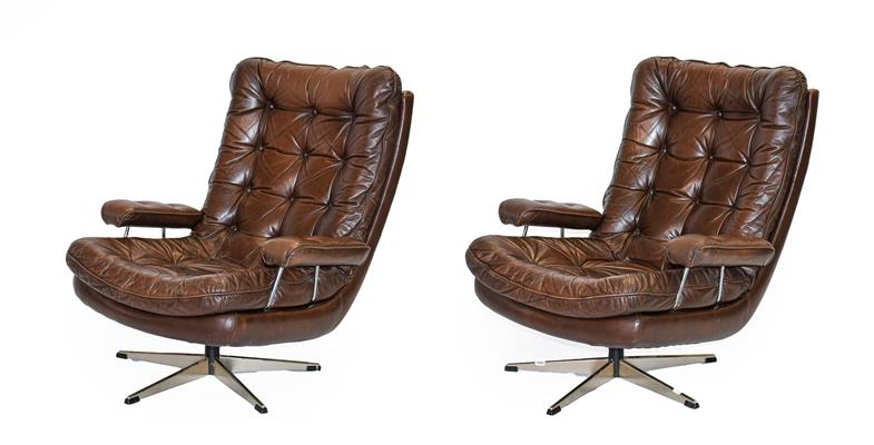A Pair of 1970's Scandinavian Buttoned Brown Leather and Chrome Lounge Chairs, five prong base