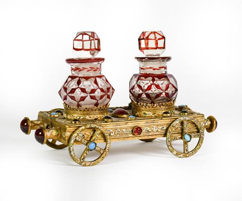 A Gilt-Metal, Gem-Set and Enameled Bottle-Stand, in the form of a flatbed rail carriage, set with