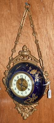 A gilt metal and enamel wall timepiece