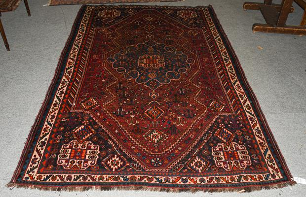 A Kashgai rug, the chestnut field with sky blue medallion framed by spandrels and ivory borders,