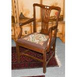 A mahogany open armchair with drop in needlework seat, with square section legs joined by a