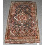A Kashgai rug, the field of tribal motifs around an ivory medallion framed by spandrels and narrow