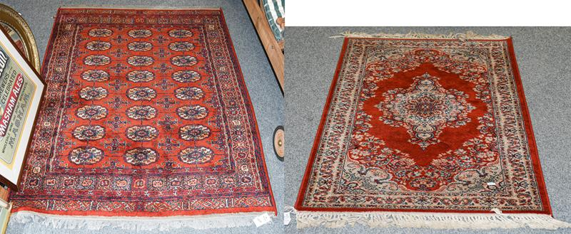 A machine made rug, the blood red field with central medallion framed meandering vine borders