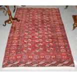 A Tekke rug, the blood red field with three colums of guls enclosed by stellar motif borders,