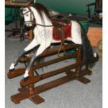 A dapple grey painted rocking horse on trestle base, one bracket stamped G&J L Ltd, 135cm long by