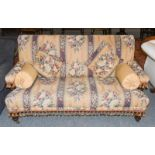 A Victorian sofa raised on turned legs and brass castors, upholstered in floral and fruiting vine
