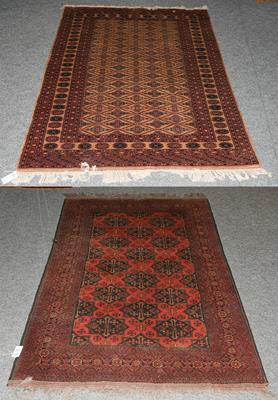 An Afghan Turkman rug, the brick red field with columns of panels enclosed by multiple narrow