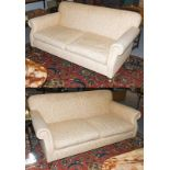 A pair of cream upholstered three seater sofas with scroll arms and moving on castors, 185cm by