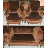 A 1920's three-piece suite comprising a sofa and two chairs in brown upholstery