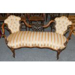 A Victorian carved walnut framed open sofa upholstered in striped fabric, 155cm long