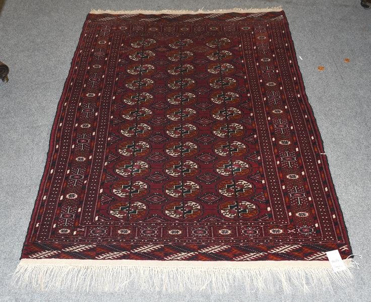 A Tekke rug, the field with three columns of guls enclosed by multiple narrow borders, 148cm by