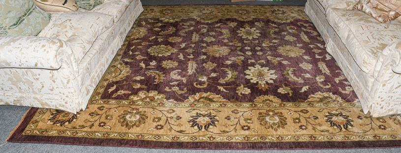 Large Indian carpet, the aubergine field with an all over design of large flower heads and vases