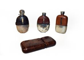 A crocodile skin cigar pouch together with three silver plated and crocodile skin mounted hip flasks