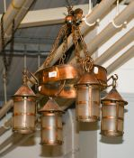An Arts and Crafts copper hanging electrolier, comprising four lanterns