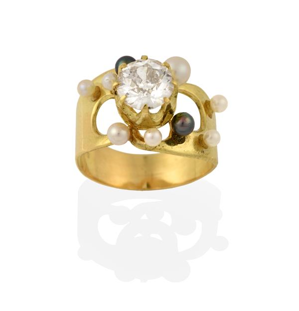 An 18 Carat Gold Diamond and Cultured Pearl Ring, the raised round brilliant cut diamond in a yellow
