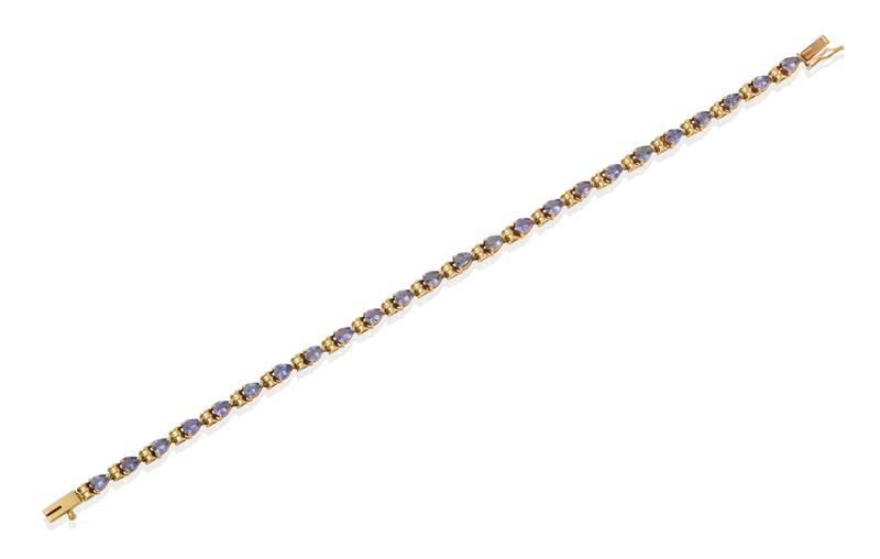 A Tanzanite Bracelet, twenty-four pear shaped tanzanites in yellow claw settings, spaced by scroll