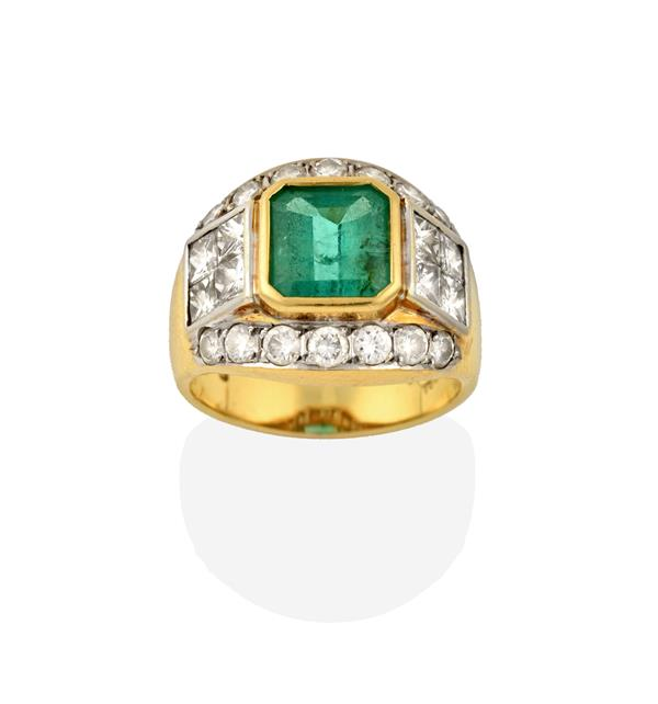 An Emerald and Diamond Ring, the emerald-cut emerald, flanked by princess cut diamonds, to a