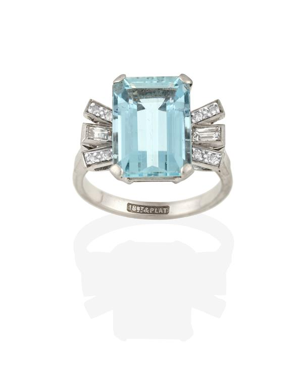 An Aquamarine and Diamond Ring, the emerald-cut aquamarine flanked by baguette cut and eight-cut