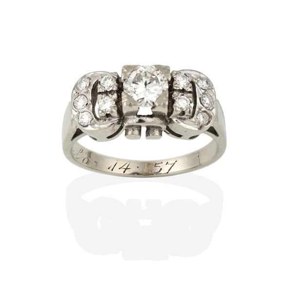 A Diamond Cluster Ring, the buckle motif set throughout with round brilliant cut diamonds, in