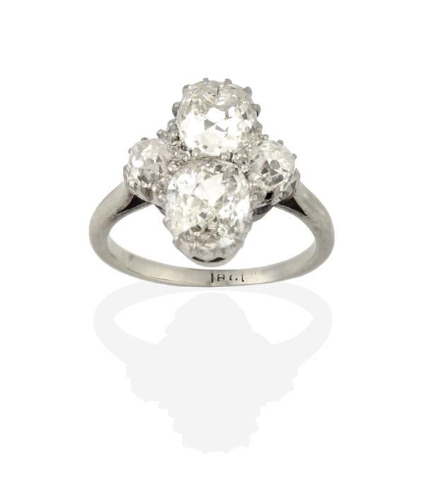 A Diamond Ring, the old cut diamonds arranged in a cross formation, in white claw settings, to a