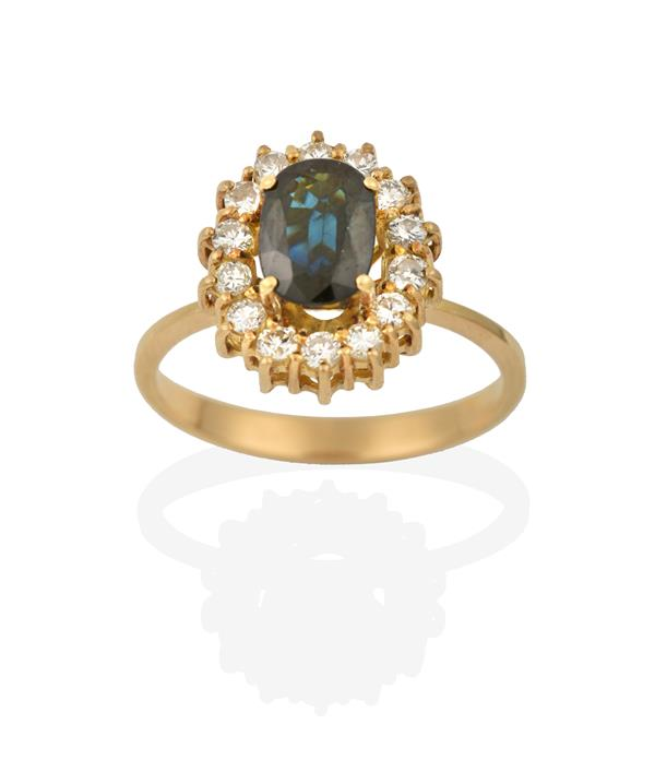 A Sapphire and Diamond Cluster Ring, the oval cut sapphire within a border of round brilliant cut