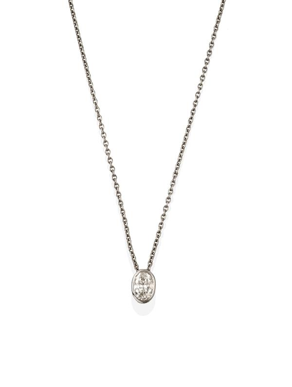 A Diamond Solitaire in a Pendant on Chain, the oval cut diamond in white rubbed over setting, on a