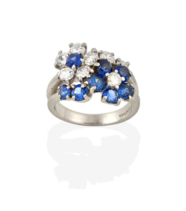A Sapphire and Diamond Cluster Ring, realistically modelled as two floral motifs, one cluster formed