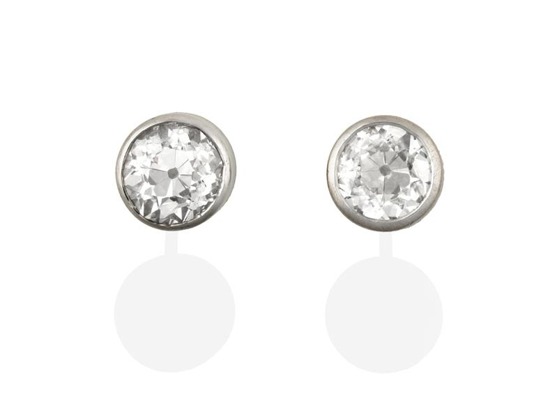 A Pair of 18 Carat White Gold Diamond Solitaire Earrings, the round brilliant cut diamonds in rubbed