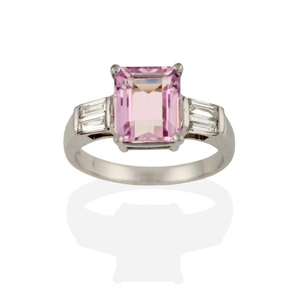 A Kunzite and Diamond Ring, the emerald-cut kunzite flanked by pairs of tapered baguette cut