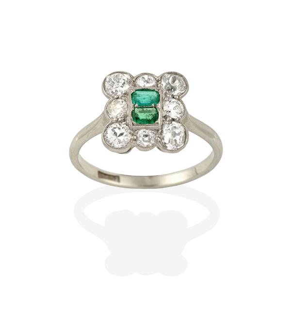 An Emerald and Diamond Cluster Ring, two emerald-cut emeralds within a border of old cut diamonds,