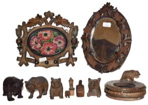 A group of carved wooden articles including Black Forest style bears, leaf carved mirror, a carved