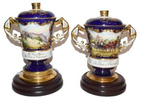 Two Aynsley twin handled cups and covers, one for Prince Philip's 70th birthday, the other for his