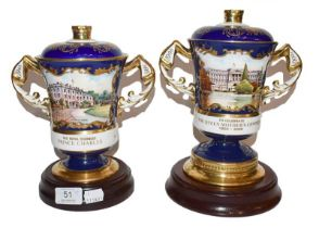 Two Aynsley twin handled cups and covers, one for the Queen Mother, the other for Prince Charles (2)