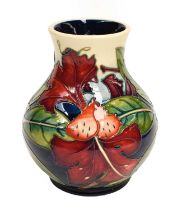 A modern Moorcroft pottery baluster shaped vase, decorated in the Simian design