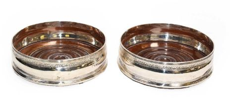 A pair of George III Irish silver bottle coasters with turned bases, bearing marks for Dublin