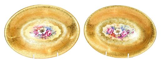 A pair of oval Royal Worcester dishes painted by Freeman with flowers under wide gilt borders (2)