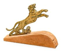A Bronzed Accessory Mascot, as an outstretched lion, mounted on a wooden base