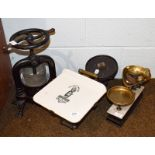 A pair of Victorian cast iron and brass grocers scales with printed pottery table, together with a